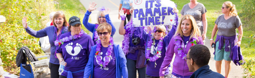 An ALS walk team, one member of which is excitedly holding a sign that reads It's Pammer Time!