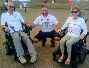Two people living with ALS posing with WALK for ALS participant and friend