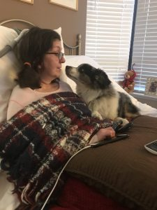 Woman living with ALS laying in bed with dog