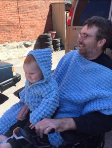 Man living with ALS holding infant son in his power wheelchair