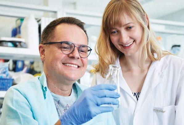 ALS researcher in the lab with a person living with ALS