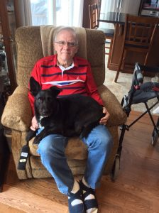 A man sitting in chair, with a black dog on his lap