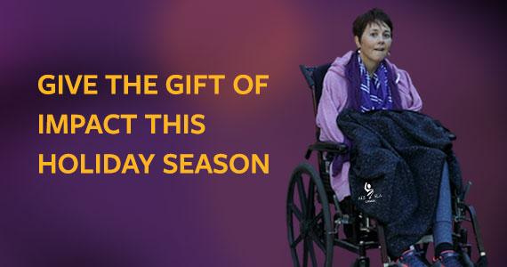 Pam in wheelchair wearing ALS Canada branded blanket across legs